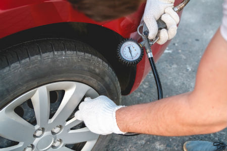 mechanic checking tire pressure on a car