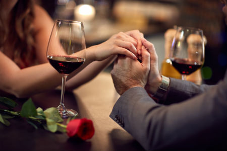 couple romantically holding hands with a rose and wine