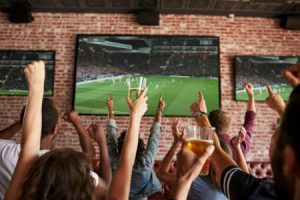 cheering people watching football on a tv