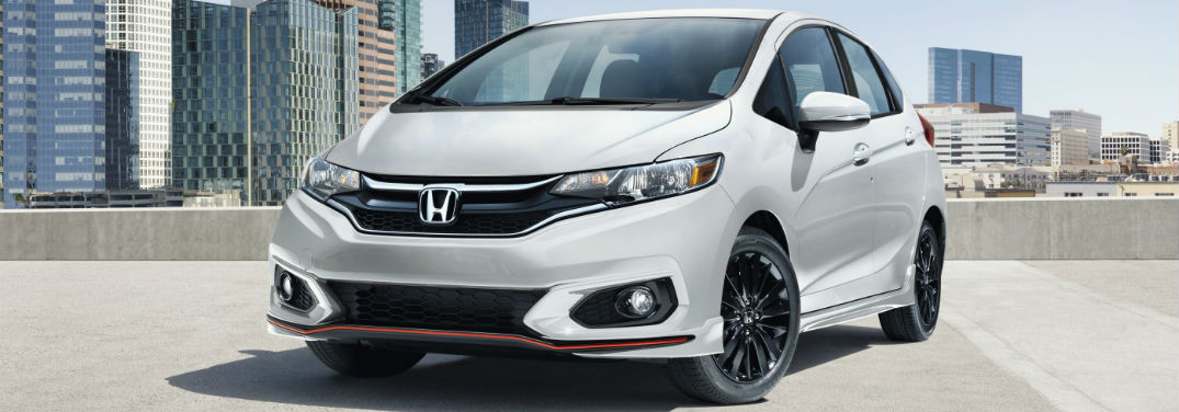 2019 Honda Fit Pricing and Features with image of 2019 Honda Fit in Platinum Pearl White parked on roof of a parking garage with view of a city in the background