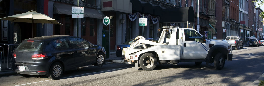 car being towed from a side street