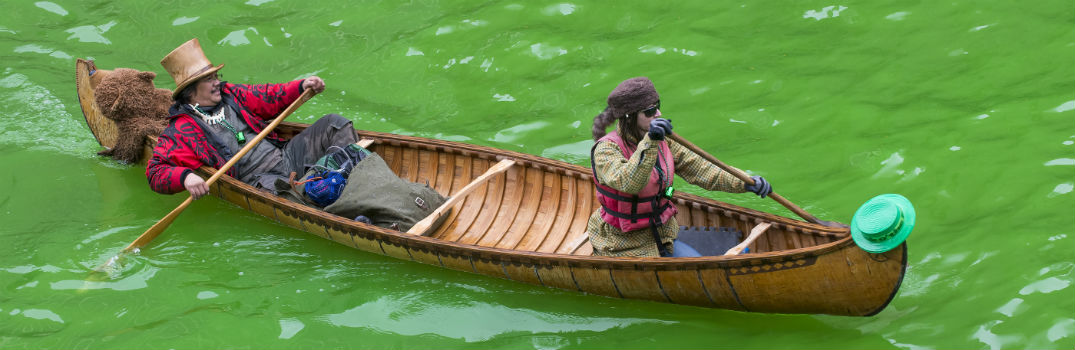 two men floating down a green river in a canoe