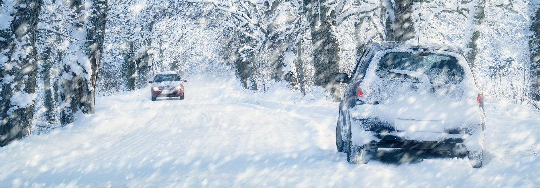 two cars driving past each other on snowy road