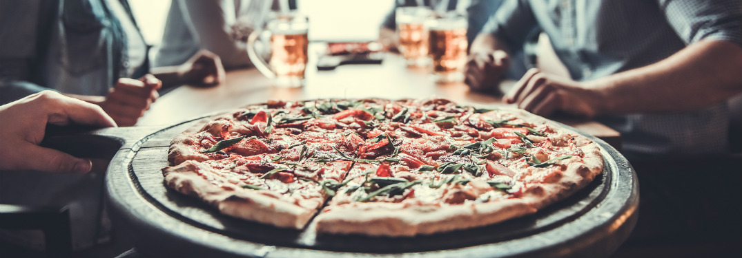 fresh pizza on plate being served to group of people on table