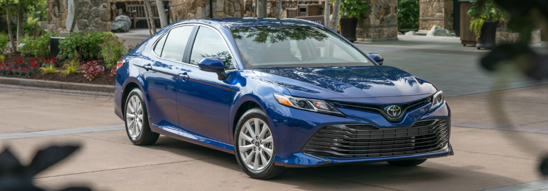 blue 2018 toyota camry in driveway of mansion