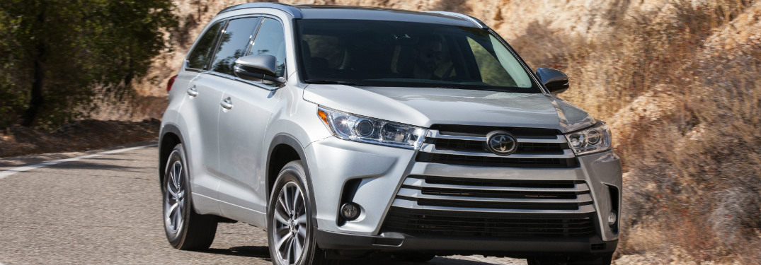 silver 2018 toyota highlander driving down road with cliff rocks behind it