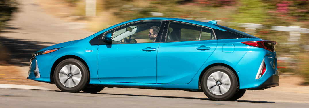 side view of blue 2018 toyota prius prime driving on road