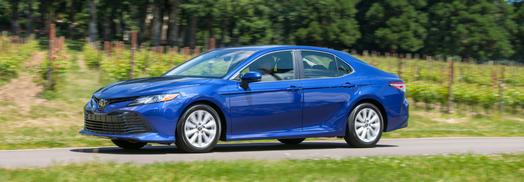 blue 2018 toyota camry driving on road with vineyard behind it