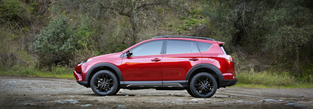 side view of red 2018 toyota rav4 on dirt path with dirt hill behind it