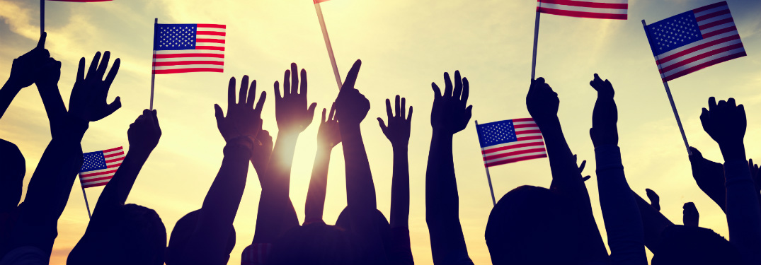 silhouettes of people with arms raised holding american flags and cheering