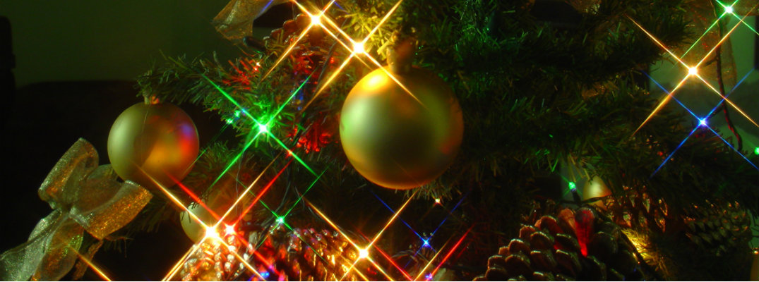 Ornaments on a Christmas tree with lights illuminating in background