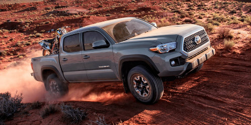 2018 Toyota Tacoma driving on desert terrain with ATV in truck bed