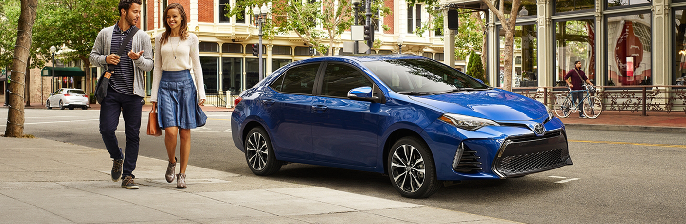 Blue 2018 Toyota Corolla parked with people observing it
