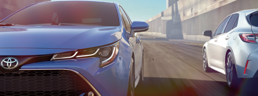Blue 2019 Toyota Corolla Hatchback driving past a white car
