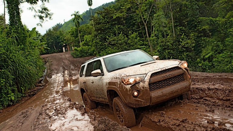 White Toyota 4Runner Covered In Mud Driving Through The Forest