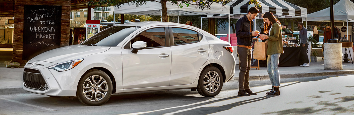White 2019 Toyota Yaris parked in front of a store