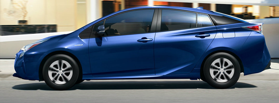 Action shot of blue 2018 Toyota Prius driving on city road in front of buildings