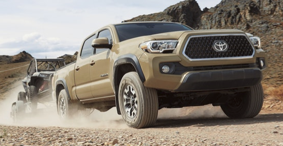 Tan 2019 Toyota Tacoma towing trailer on dirt road