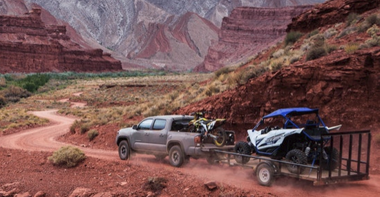 2019 Toyota Tacoma driving on mountainous trail pulling trailer