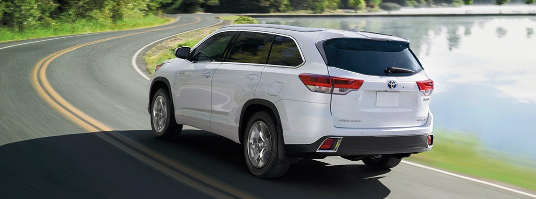 Rear view of white 2019 Toyota Highlander driving near water
