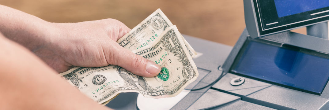 Hand holding dollar bills at cash register