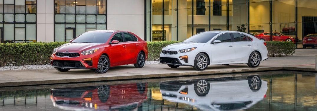 Two 2019 Kia Forte Models Parked on concrete next to a reflecting pool in front of a glass building