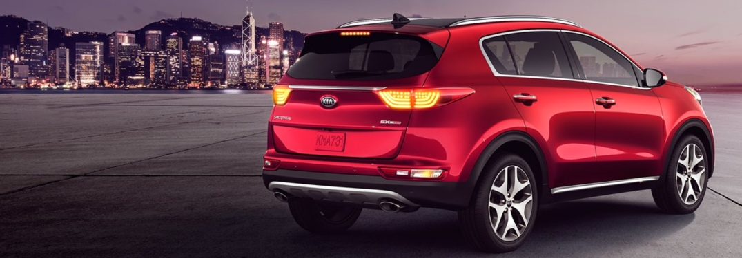 Red 2019 Kia Sportage parked in front of city skyline