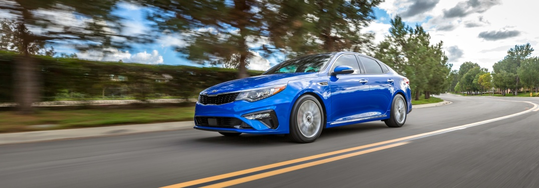 Blue 2019 Kia Optima driving on open road