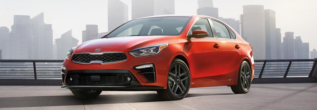 Red 2019 Kia Forte parked in front of city skyline