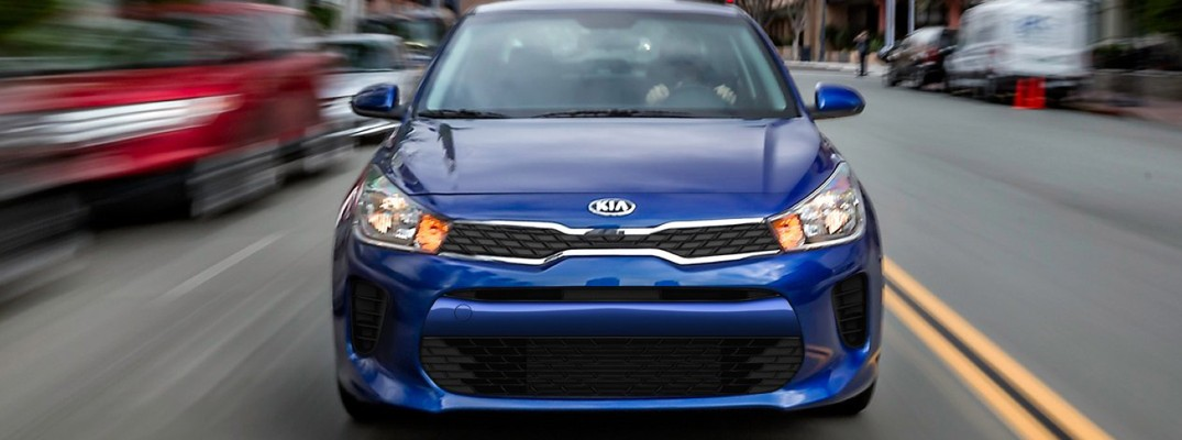 2020 Kia Rio blue exterior front driving fast past parked
