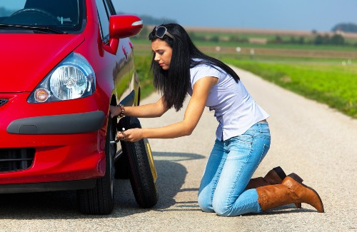 woman changing tire of red car on side of road