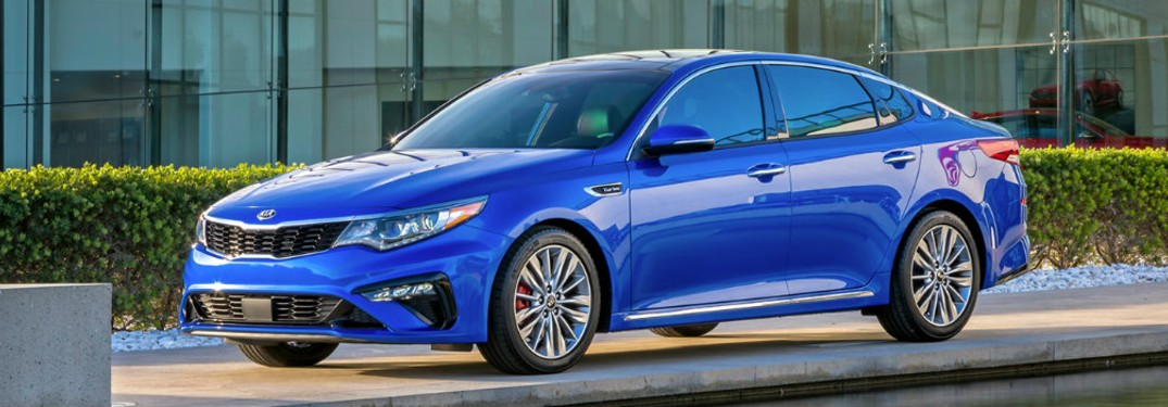 2020 Kia Optima blue exterior front driver side parked on sidewalk building and bushes in background