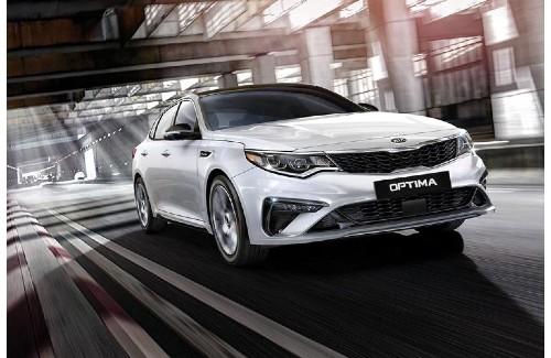 2020 Kia Optima white exterior front passenger side driving inside building