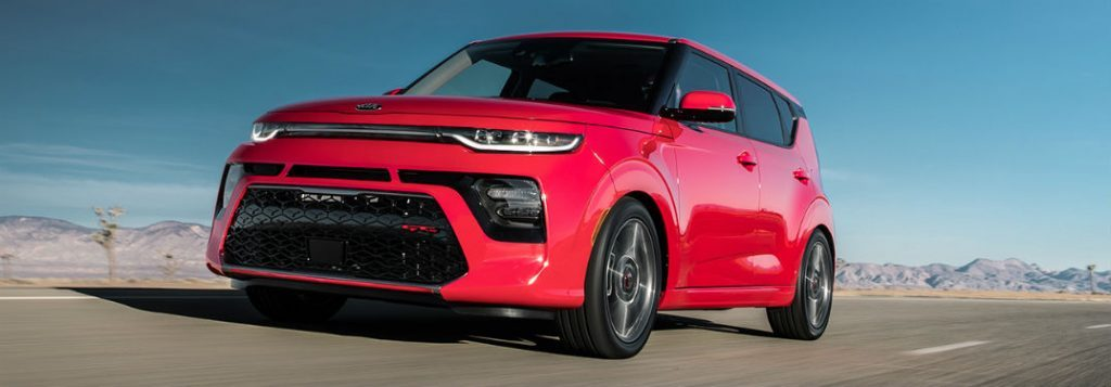 2020 Kia Soul red exterior front fascia driver side driving past joshua trees and mounds
