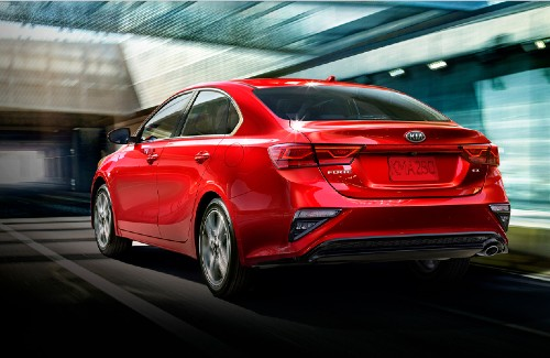 2021 Kia Forte red exterior rear fascia driver side driving on road