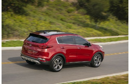 2021 Kia Sportage exterior overhead rear shot with dark red paint color driving on a highway near green hills