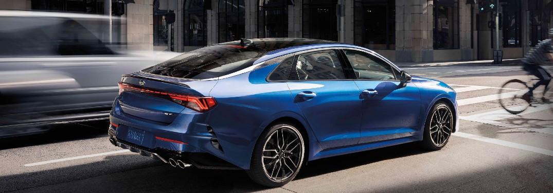 2021 Kia K5 blue exterior rear fascia passenger side driving in city