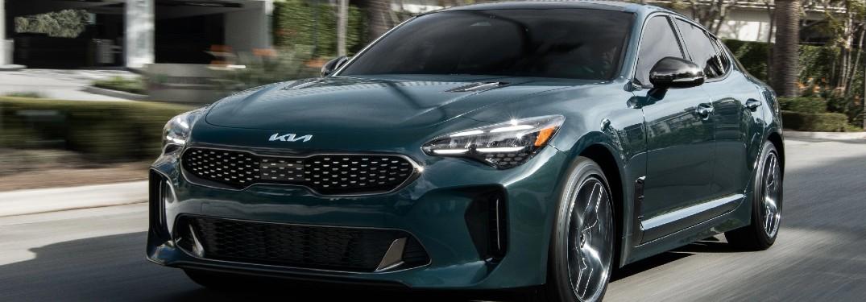 2022 Kia Stinger dark green exterior front fascia driver side driving in city
