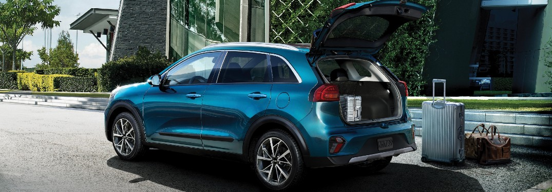 blue 2021 Kia Niro parked outside building tailgate open suitcase on ground