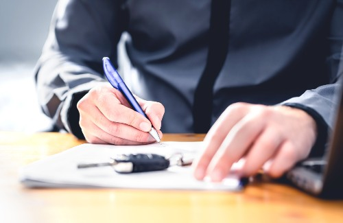 person signing papers for car with keys on papers