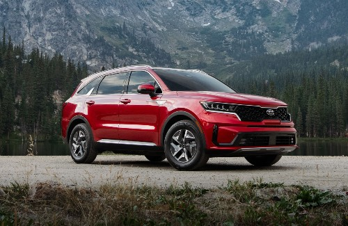 red 2021 Kia Sorento Hybrid front fascia passenger side parked on gravel with evergreen forest and mountains behind