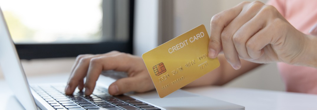 woman looking at credit card while shopping online