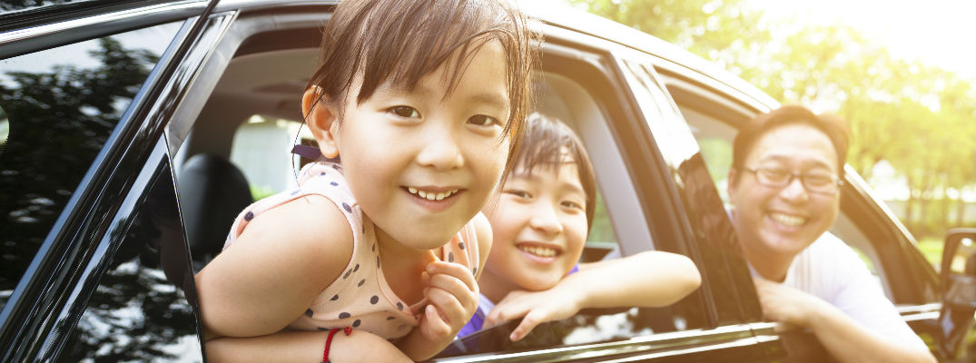 Two smiling kids and a smiling dad in their car