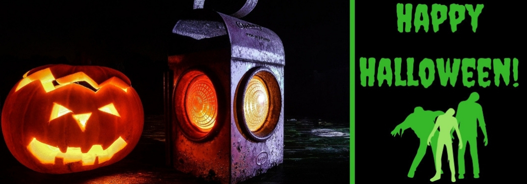 Picture of a Lit Jack-o-Lantern and Train Lantern on a Table and Black Background with Green Zombie Graphic and Green Happy Halloween Text
