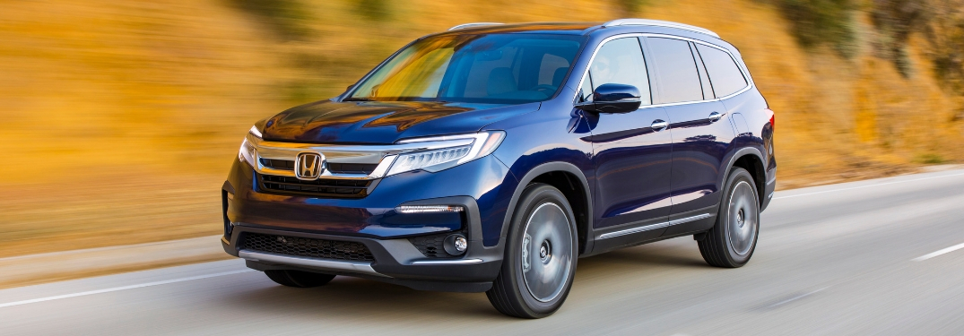 Blue 2019 Honda Pilot Driving on a Country Road with Fall Foliage in the Background
