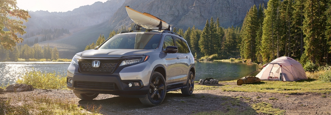 Silver 2019 Honda Passport with Roof Rack and Canoe Parked at a Campsite by the Lake