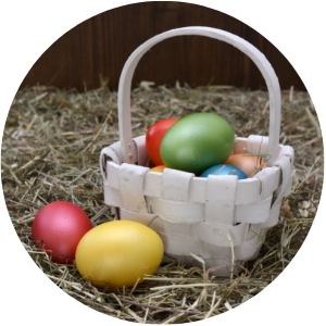 White Easter Basket with Colorful Easter Eggs on Straw Floor