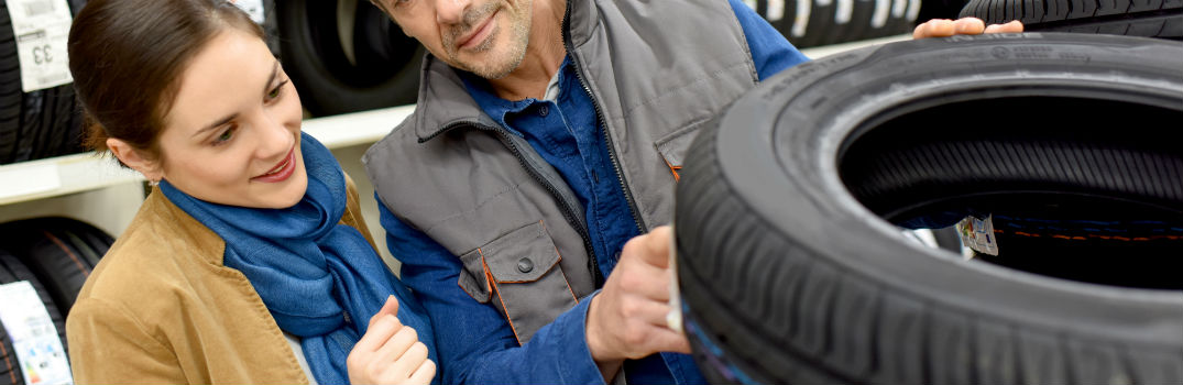 man and woman looking at a tire in a store