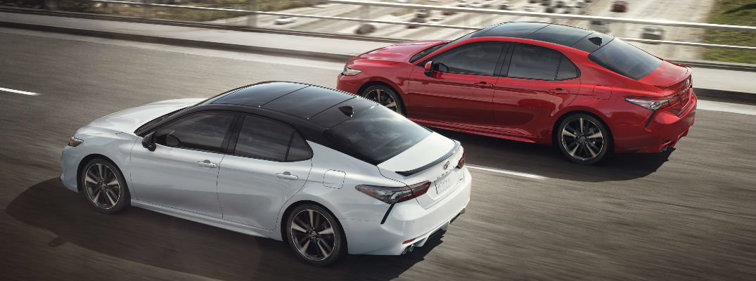 2018 toyota models. white and red 2018 toyota camry xse models on the freeway with panoramic moonroof