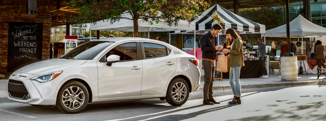 White 2019 Toyota Yaris Sedan and Couple at a Farmers Market